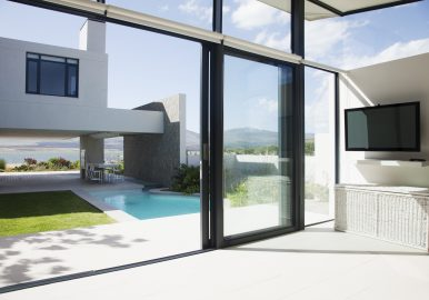 View of patio and swimming pool through sliding doors of modern house